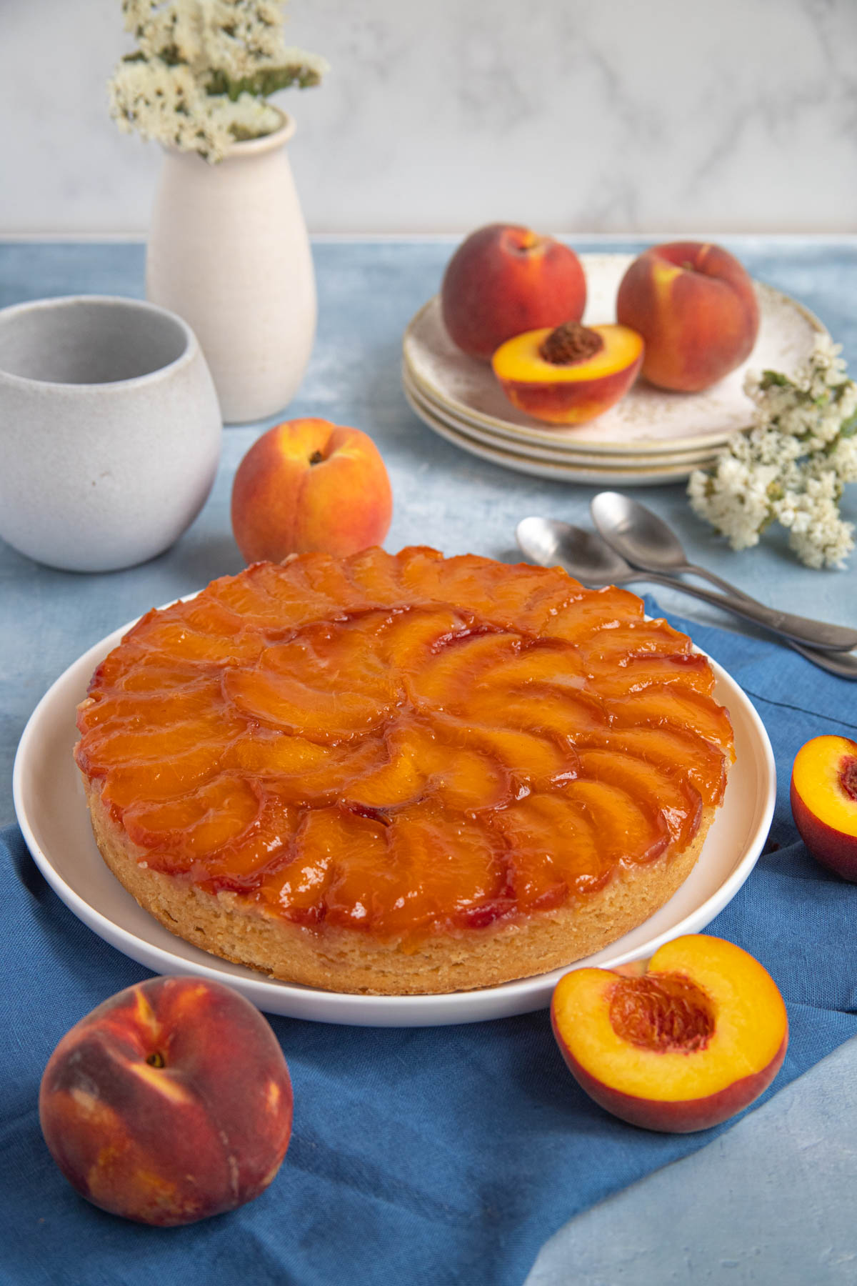 Peach Bourbon Upside Down Cake on a platter surrounded by fresh peaches with fresh flowers and a coffee mug in the background