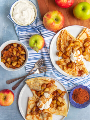 Two plates of apple cinnamon crepes with whipped cream. A bowl of cinammon apples and a bowl of whipped cream next to the plates