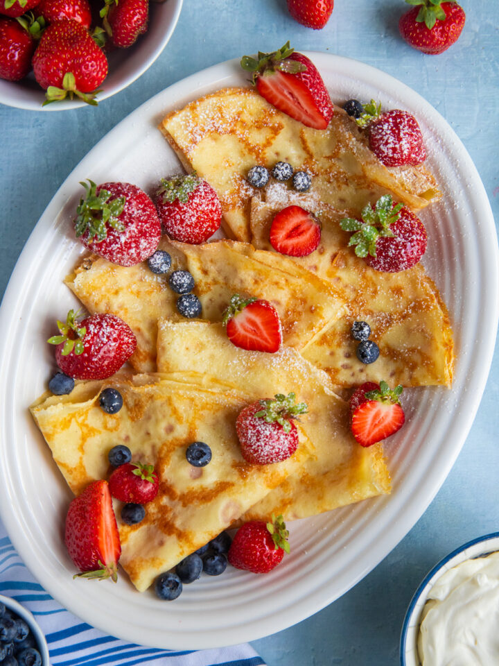 Platter with folded crepes, topped with strawberries, blueberries and dusted with powdered sugar