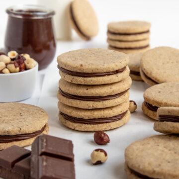 A stack of hazelnut chocolate sandwich cookies next to a bowl hazelnuts and jar of chocolate ganache