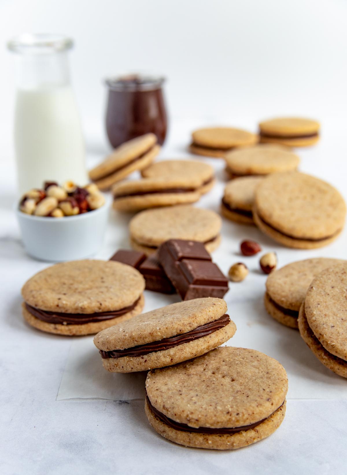 Hazelnut Chocolate Sandwich Cookies next to a class of milk and a bowl of hazelnut cookies