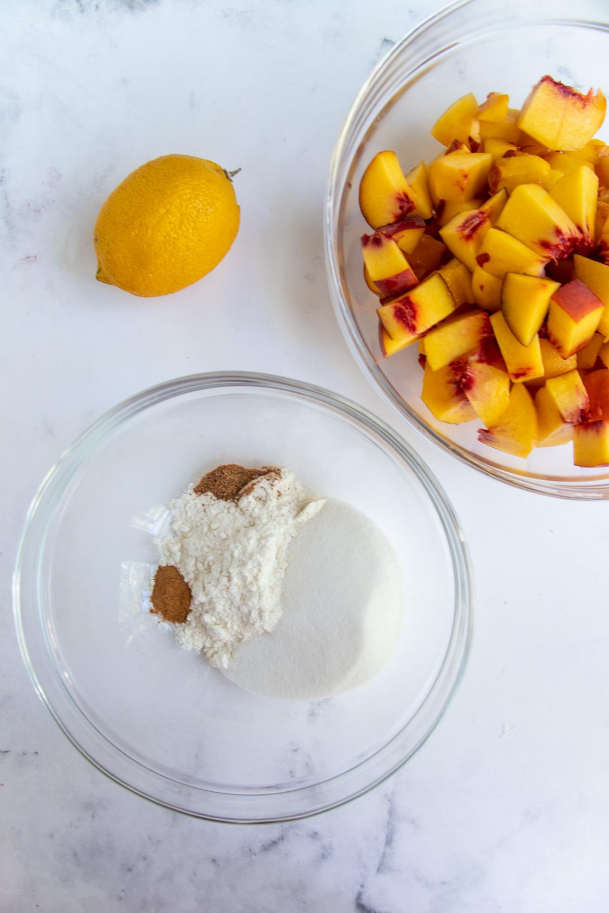 Bowl of peaches and a bowl of flour, sugar, cinnamon and nutmeg