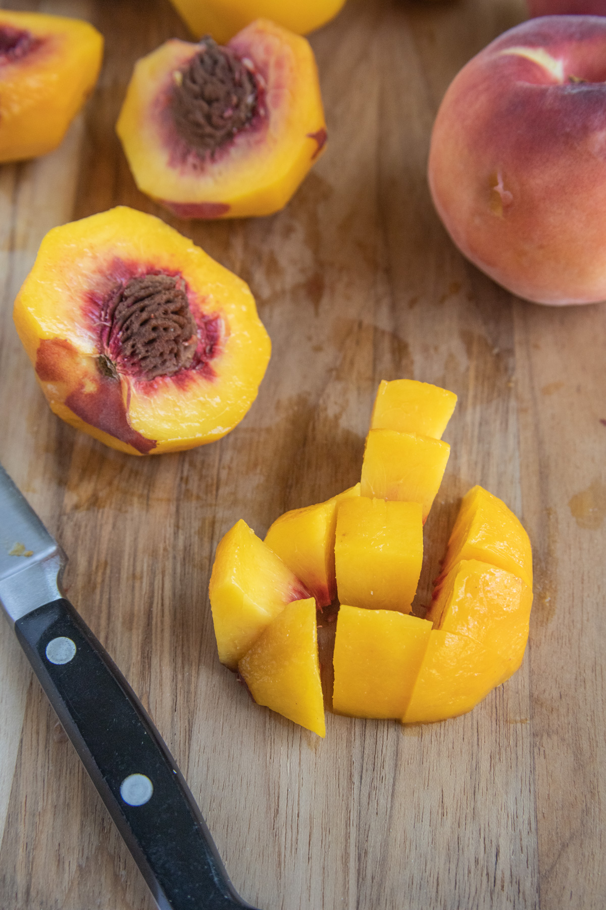 Chopped peaches on a wooden cutting board