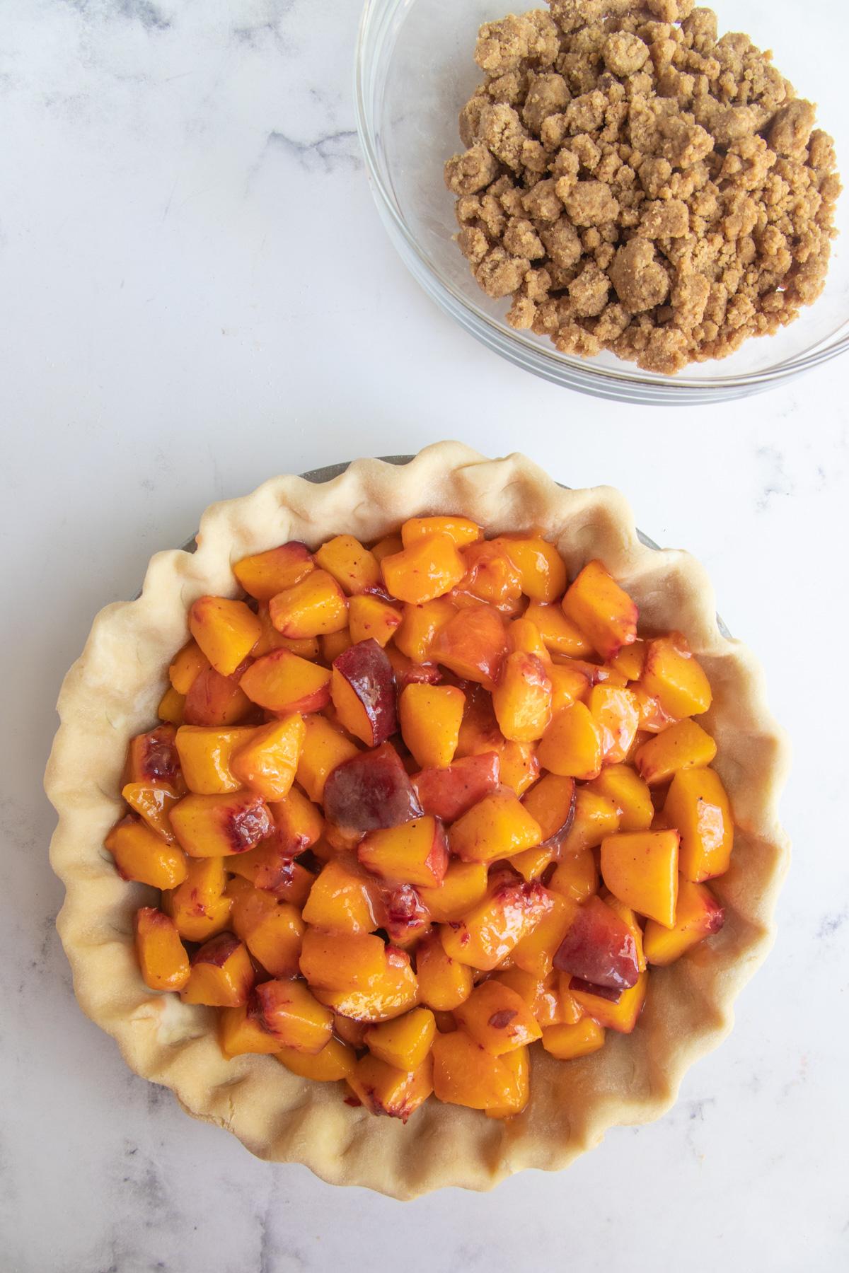 Peaches placed in prepared pie dough next to the bowl fo brown sugar crumble