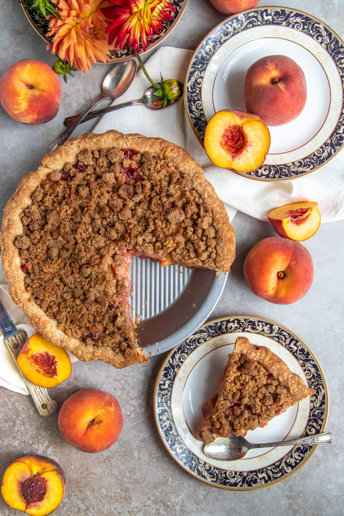 Peach crumble pie next to a dessert plate with a slice of pie.  Pie is surrounded by whole and cut peaches