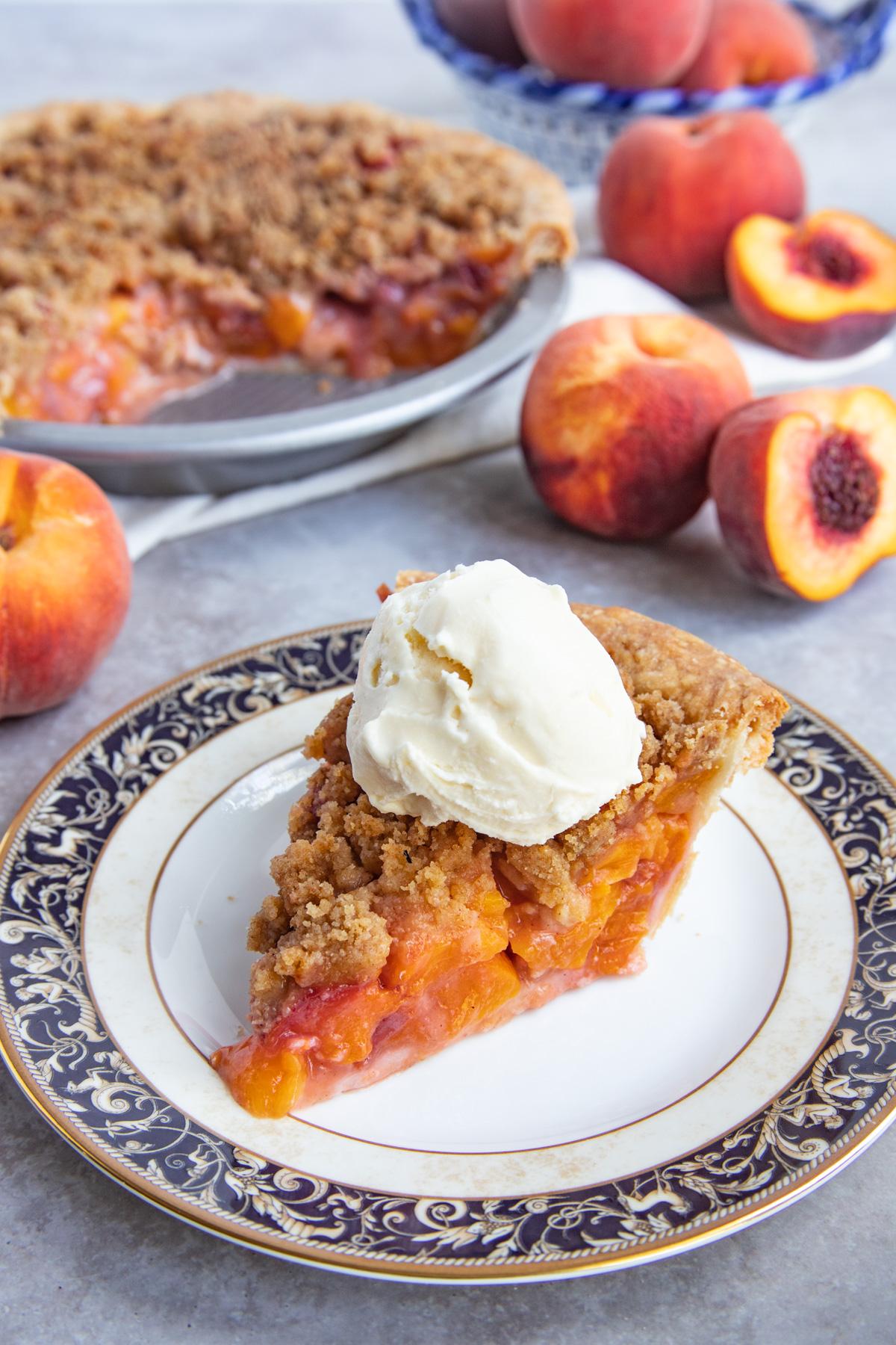 Slice of peach crumble pie on dessert plate with scoop of vaniila ice cream