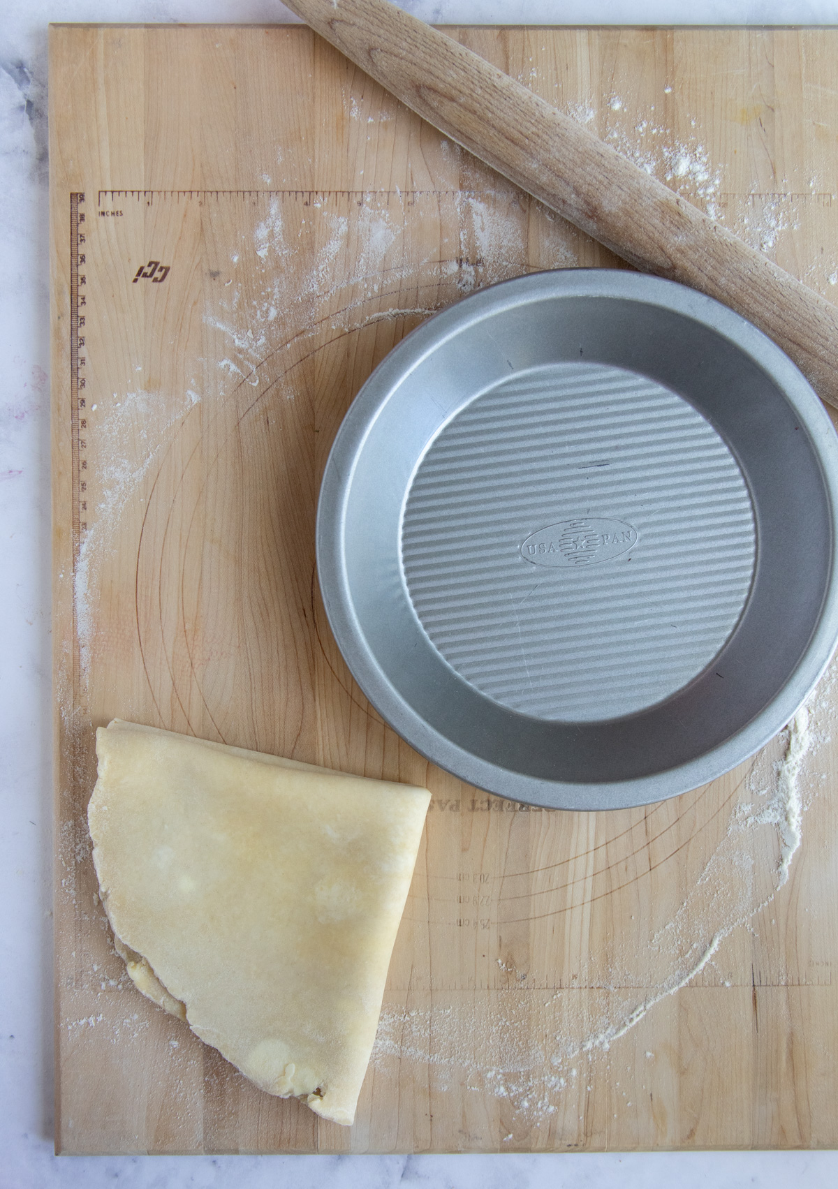 Pie plate next to pie dough which is folded into quarters before placing it in the pie plate