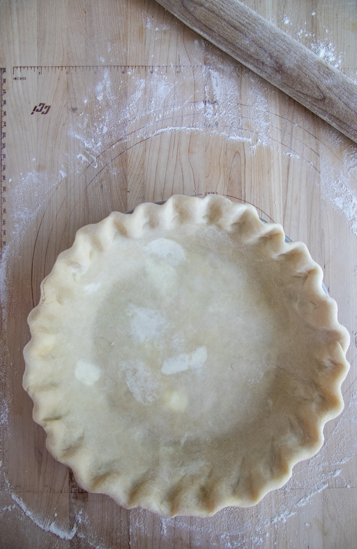 Pie dough in the pie pan with crimped edges