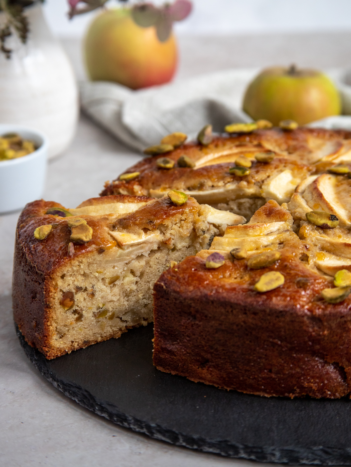 Apple cake on black cake plate surrounded by apples and an antique cutting knife.