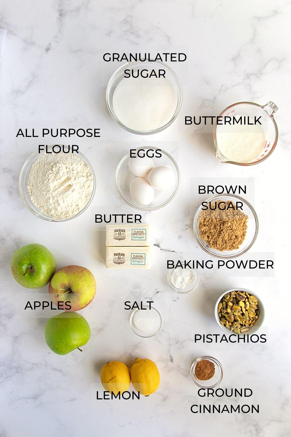 Apple Cake Ingredients - White sugar, buttermilk, brown sugar, baking powder, pistachios, ground cinnamon, lemons, apples, salt. butter, eggs, all-purpose flour