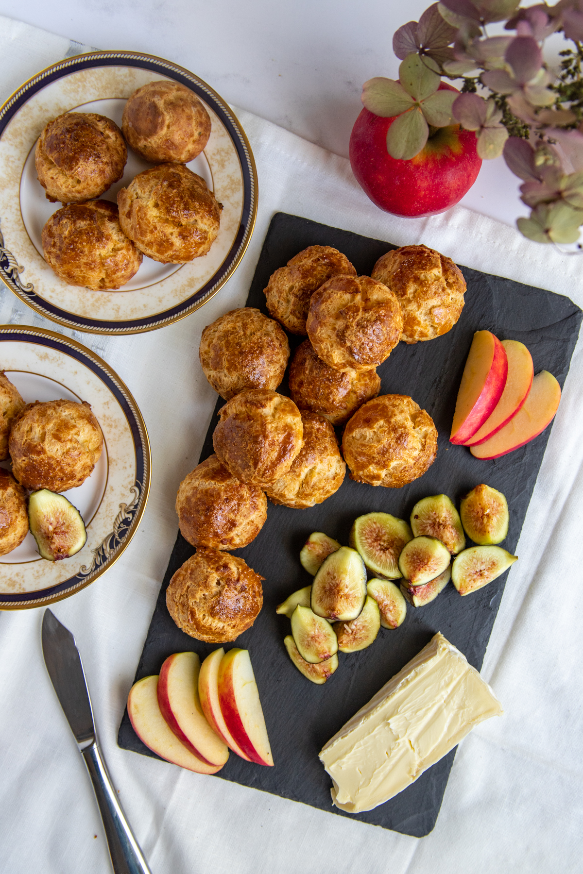Gougeres on a cheese board with apples, figs and brie