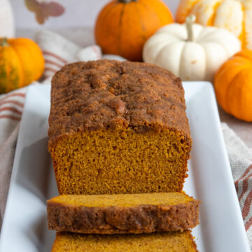 Pumpkin Bread on white platter with mini pumpkins in the background